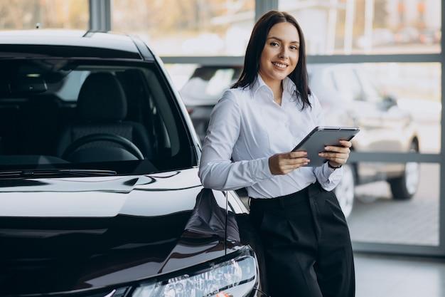 Vendedora en sala de exposición de coches vendiendo coches