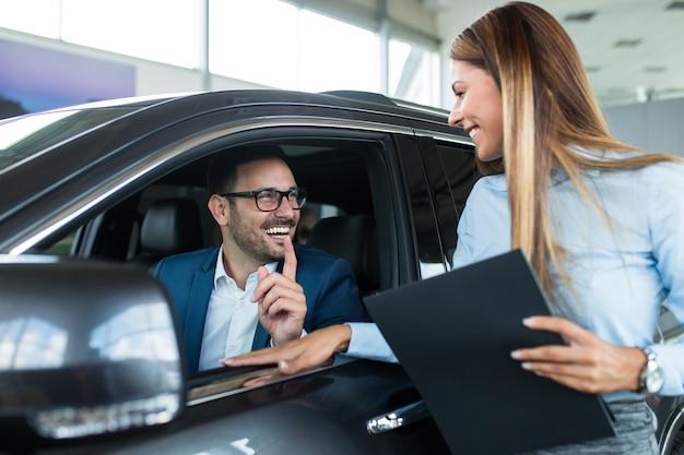 Vendedora en la sala de exposición del concesionario hablando con el cliente y ayudándolo a elegir un auto nuevo para él.