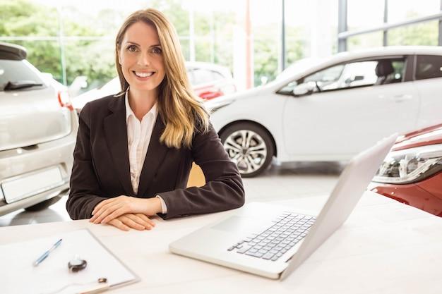 Vendedora sonriente detrás de su escritorio en la sala de exposiciones de automóviles nuevos