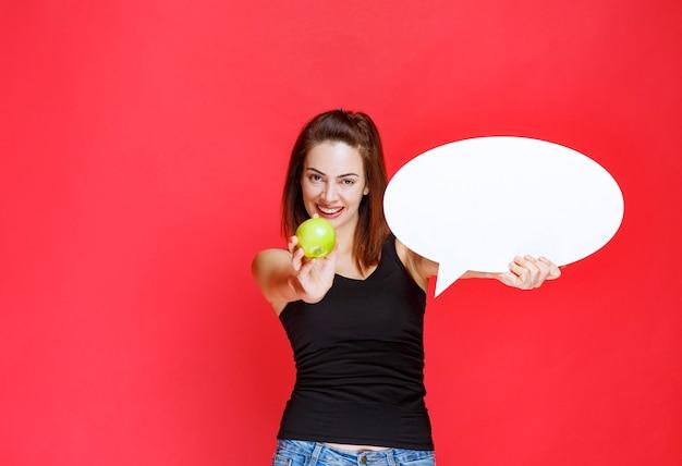 Vendedora sosteniendo una manzana verde y un tablero de información ovale y dando la manzana al cliente