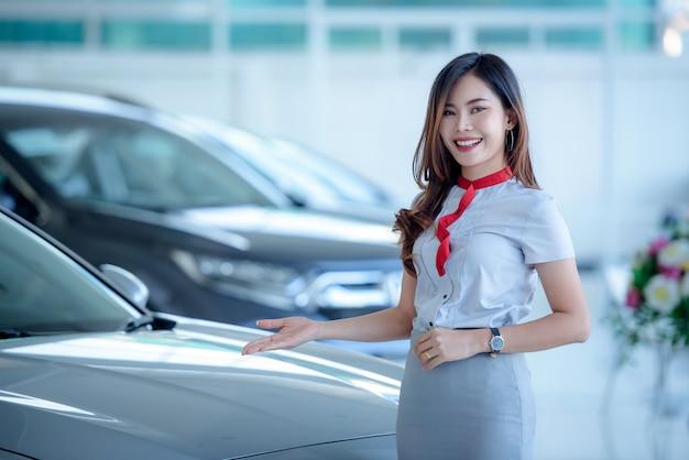 Los vendedores asiáticos hermosos están felices de vender autos nuevos en la sala de exposición y hacer que los clientes vengan a comprar autos en los concesionarios.