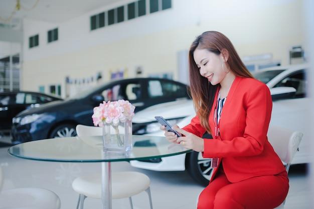 Vendedores de automóviles, mujeres hermosas, mujeres asiáticas que hablan por teléfono con los clientes para vender automóviles nuevos en las salas de exhibición de automóviles.