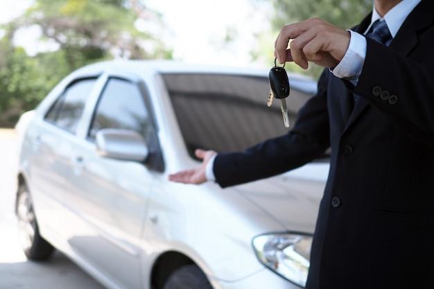 Vendedores de autos y llaves presentando el comercio de autos
