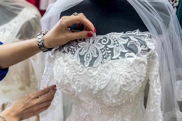 Vendedores de manos corrigiendo velo de novia en maniquí en salón