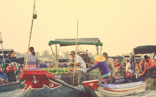 Vendedores vietnamitas comprando sandía en el mercado flotante de nga nam