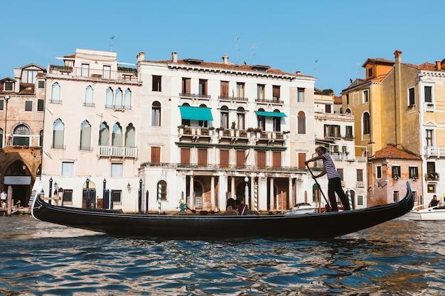 Venecia, italia - 2 de julio de 2018: fotografía en primer plano de góndola con gente y gondolero, en el fondo los edificios históricos del gran canal (canal grande). día soleado de verano y cielo azul.