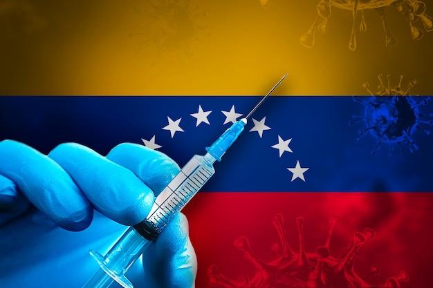 Venezuela campaña de vacunación covid19 mano en un guante de goma azul sostiene la jeringa frente a la bandera