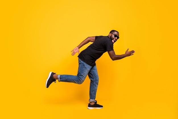 ¡vengo gangas! foto lateral de perfil de longitud completa de un chico afroamericano loco y funky ir a caminar, correr, ventas increíbles, gritar, usar ropa moderna aislada sobre una pared de color amarillo