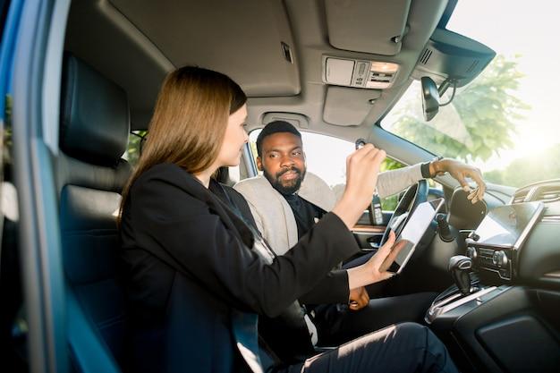 Venta y alquiler de automóviles, concepto de personas. feliz hombre africano y mujer caucásica concesionario de automóviles con tablet pc sentado en coche nuevo. mujer gerente de ventas tiene las llaves del auto y muestra el contrato de alquiler en tableta