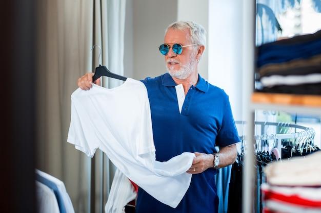 Venta. anciano elegante con gafas de sol sosteniendo una percha con camiseta blanca mientras expresa interés en el proceso de compra