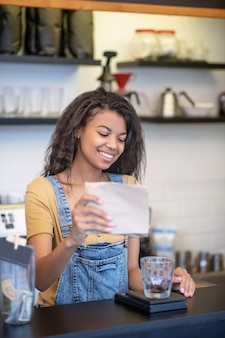 Venta de café. sonriente a mujer joven con cabello largo y oscuro vertiendo granos de café en vidrio mientras está de pie detrás de la barra en la cafetería