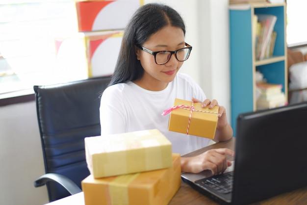 Venta de comercio electrónico en línea envío compras en línea, entrega y orden de inicio concepto de trabajo de propietario de una pequeña empresa - mujer joven empacando una caja de cartón, entrega de paquetes al cliente pago contra reembolso
