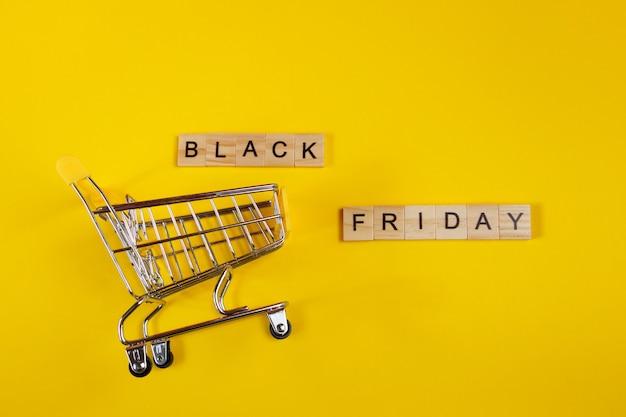 Venta y concepto de viernes negro. mini carro de la compra sobre un fondo amarillo.