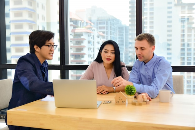 Venta hombre presente a pareja cliente en venta inmobiliaria