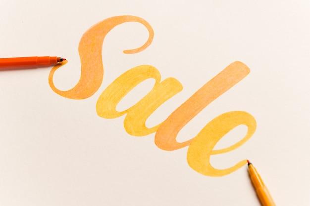 Venta de letras pintadas de naranja sobre fondo blanco.