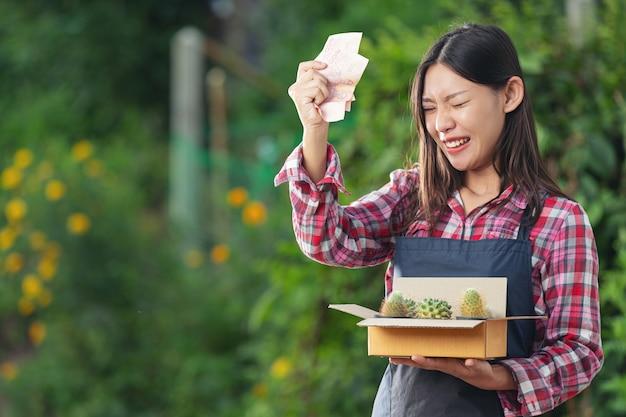 Venta de plantas en línea; la mujer se alegra mientras sostiene el dinero y la caja de envío llena con macetas de plantas