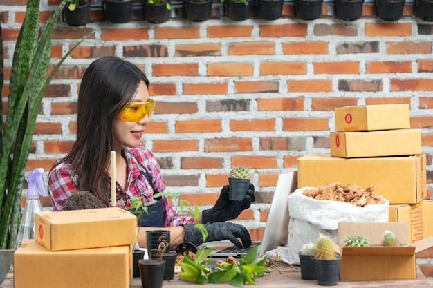 Venta de plantas en línea; mujer sosteniendo una maceta de planta y usando laptop