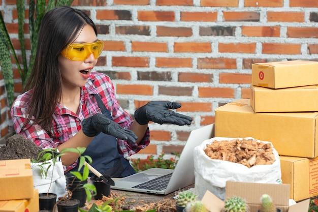 Venta de plantas en línea; las mujeres se alegran mientras usan la computadora portátil