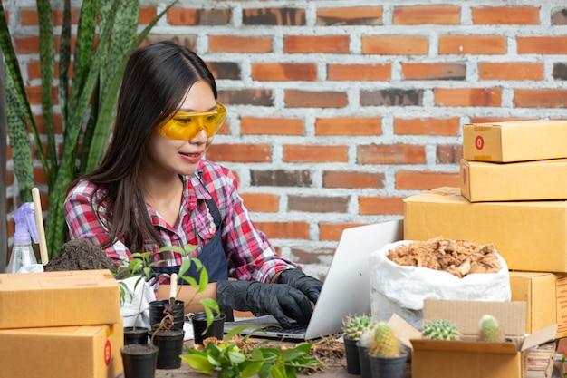 Venta de plantas en línea; mujeres sonriendo mientras usan laptop