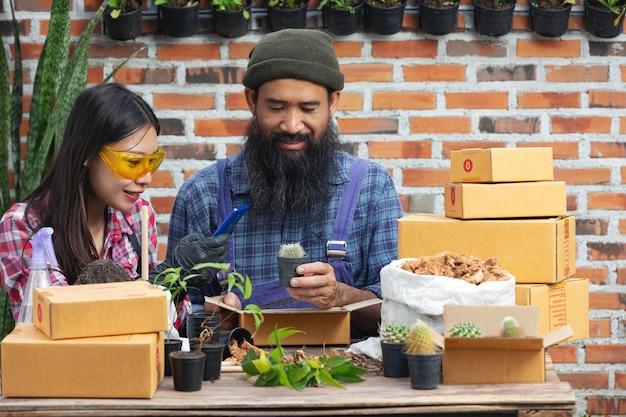 Venta de plantas en línea; parejas felices tomando fotos de plantas por teléfono móvil