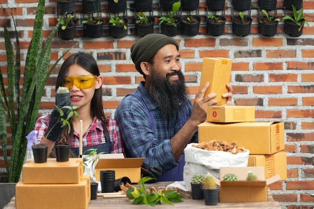 Venta de plantas en línea; vendedores sonriendo y sosteniendo una maceta y una caja de envío en sus manos