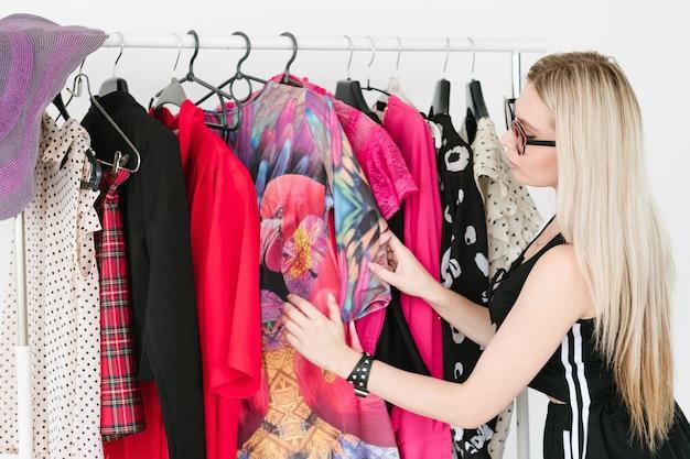 Venta de ropa de moda. colorida selección de atuendos elegantes y de moda en una boutique. mujer eligiendo ropa nueva