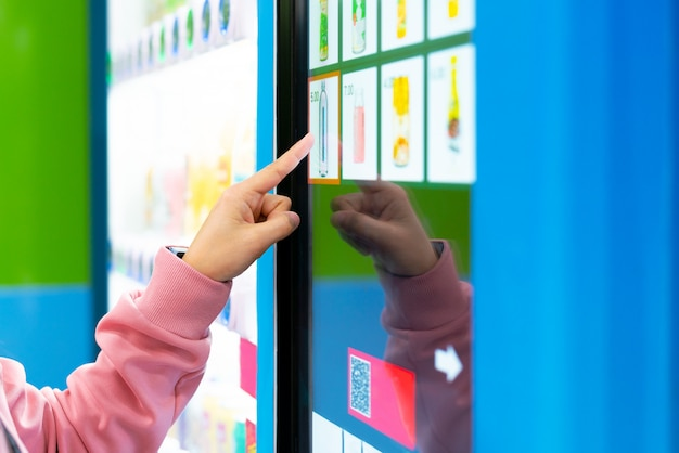 Venta, tecnología y concepto de consumo, compra de mujer con máquina expendedora.