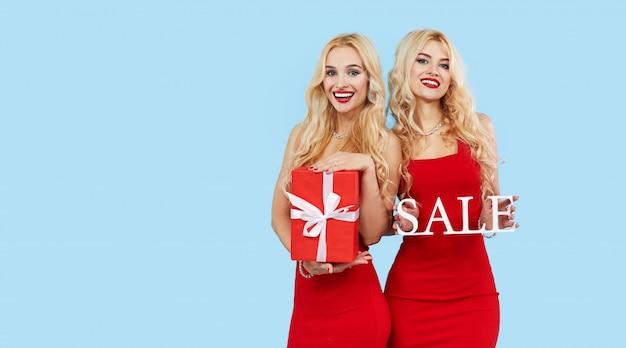 Venta de vacaciones. mujeres felices con cajas de regalo en vestidos rojos