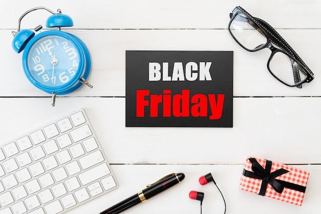 Venta de viernes negro con caja de regalo, gafas, bolígrafo y reloj despertador en mesa de madera