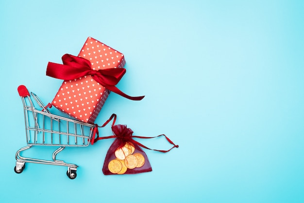 Venta de viernes negro, carrito de compras y caja de regalo con dinero de bolsillo.