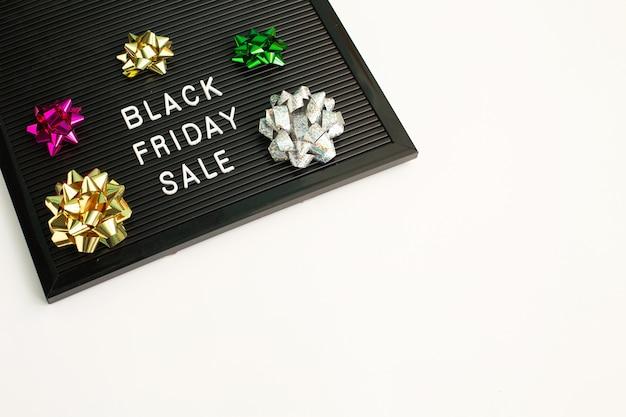 Venta de viernes negro en tablero de letras negro con cinta de regalo