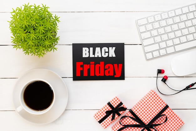 Venta de viernes negro con taza de café, mesa de planta, caja de regalo sobre fondo de madera blanco