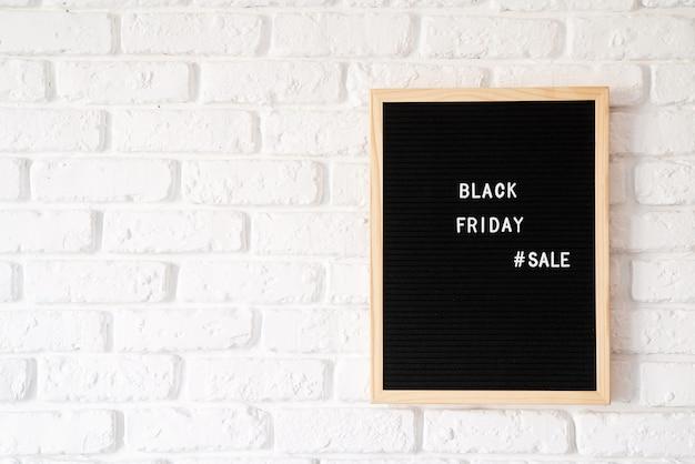 Venta de viernes negro de texto en pizarra negra sobre pared de ladrillo blanco con espacio de copia