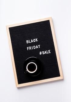 Venta de viernes negro de texto en pizarra negra con taza de café