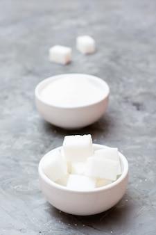 Ventajas del azúcar refinada sobre el azúcar granulada. dos tipos de azúcar en tazones blancos sobre la mesa, uno al lado del otro