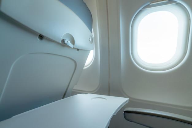 Ventana de avión con luz solar blanca. mesa de bandeja de avión de plástico vacía en el respaldo del asiento. ventana de avión de clase económica.