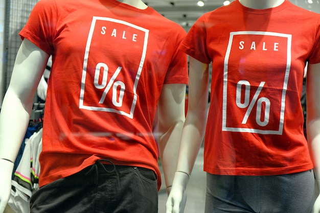 Ventana de boutique con dos maniquíes en camisetas con carteles venta de publicidad para ropa deportiva.