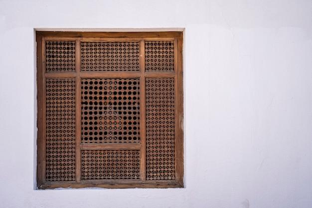 Ventana cerrada con rejas de madera en una vieja pared blanca de una casa en la calle de egipto en sharm el sheikh, cerrar, espacio de copia