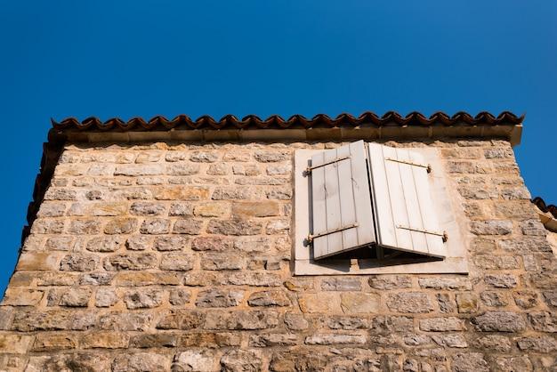 Ventana con contraventanas en un antiguo edificio de piedra