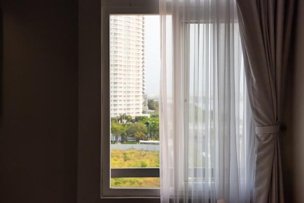 Ventana con cortinas o cortina ciega junto a la cama, concepto de decoración interior.