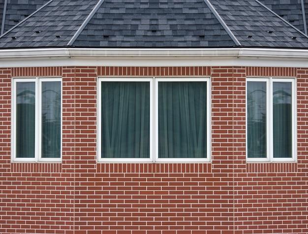 La ventana de diseño clásica del vintage en ladrillo rojo resistido bloquea el fondo de la pared de la cerca.