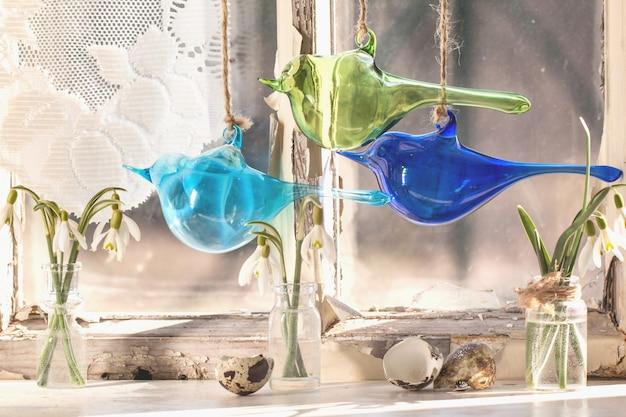 Ventana interior con pájaros de cristal y campanillas