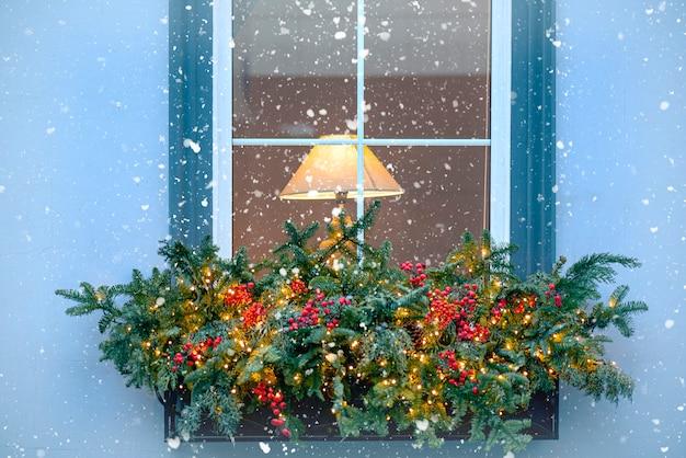 Ventana de invierno con lámpara y guirnaldas exterior de una casa antigua durante nevadas