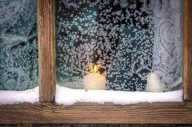 Una ventana con marco de madera, patrones helados. una vela arde fuera de la ventana.