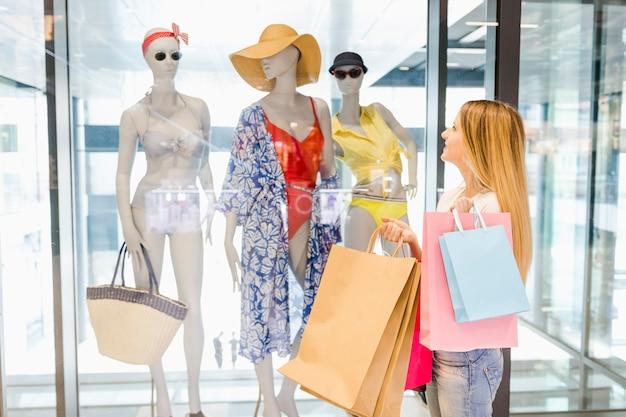 Ventana de mujer hermosa de compras en el centro comercial