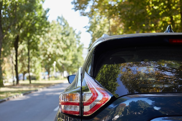 Ventana trasera del coche azul aparcado en la calle en un día soleado de verano, vista trasera. maqueta para calcomanías o calcomanías