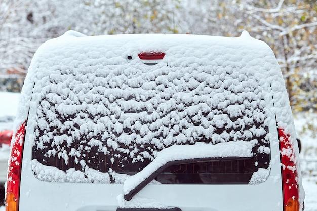 Ventana trasera del coche blanco aparcado en la calle en día de invierno, vista trasera. maqueta para calcomanías o calcomanías
