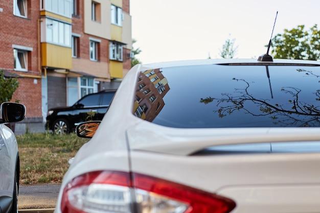 Ventana trasera del coche blanco aparcado en la calle en un día soleado de verano, vista trasera. maqueta para calcomanías o calcomanías