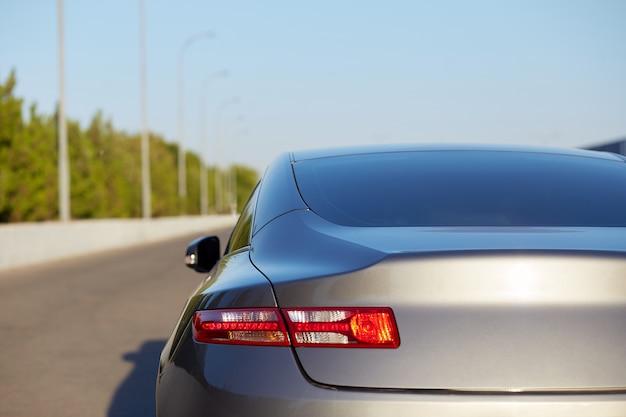 Ventana trasera del coche gris aparcado en la calle en un día soleado de verano, vista trasera. maqueta para calcomanías o calcomanías