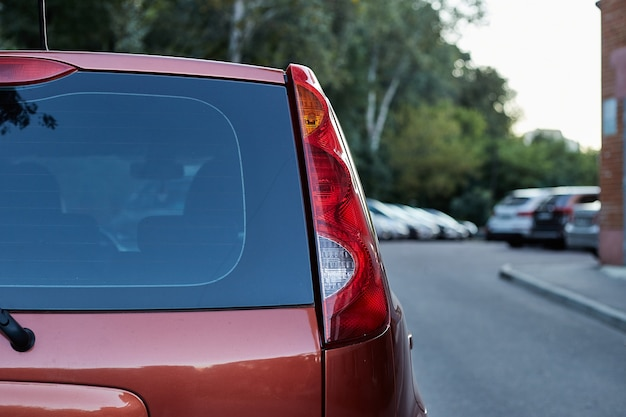 Ventana trasera del coche rojo aparcado en la calle en un día soleado de verano, vista trasera. maqueta para calcomanías o calcomanías